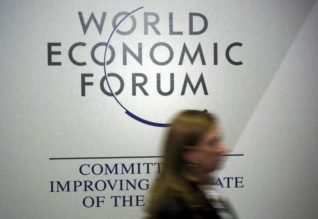 A person passes by a logo of the World Economic Forum (WEF) in the congress centre during the annual meeting of the World Economic Forum (WEF) in Davos, Switzerland Қаңuary 20, 2016.  REUTERS/Ruben Sprich